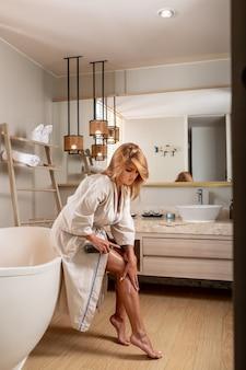 Una bionda in un accappatoio bianco in posa olio rasterizzato da una bottiglia sulla sua gamba mentre era seduto sul bagno. cura del corpo. olio per il corpo. avvicinamento. cosmetici per la cura del corpo. foto verticale.