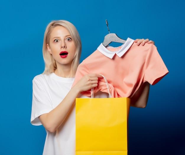 Bionda in maglietta bianca con borsa della spesa e vestito sulla gruccia sullo spazio blu