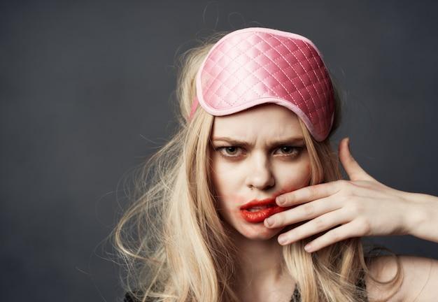 Una bionda con un trucco luminoso sul viso e una maschera per dormire rosa