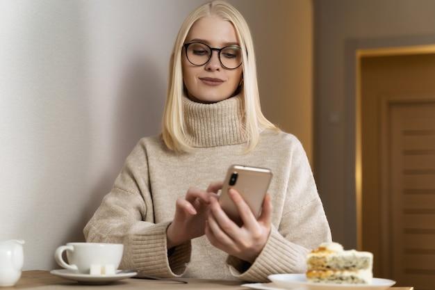 Una bionda con i capelli sciolti e gli occhiali cerchiati di nero siede a un tavolo con un caldo maglione beige.