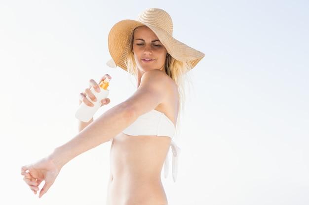 Donna bionda che applica crema solare