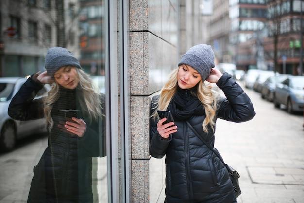 Donna bionda che controlla il suo smartphone
