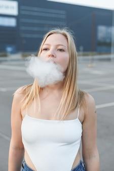 Donna bionda in città con sigaro elettronico vaping in maglietta bianca all'aperto