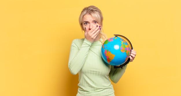 Donna bionda che copre la bocca con le mani con un'espressione scioccata e sorpresa, mantenendo un segreto o dicendo oops