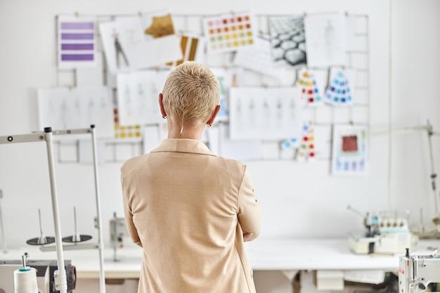 Il rivestimento beige del progettista della donna bionda sta vicino all'attrezzatura di cucito in officina leggera