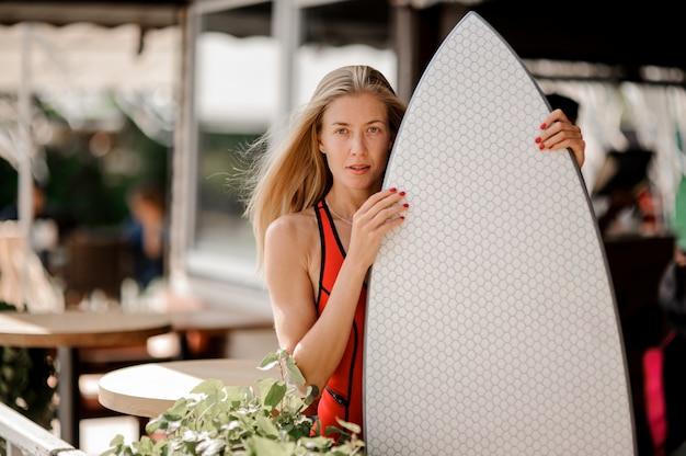 La donna bionda si è vestita in costume da bagno rosso con un wakeboard