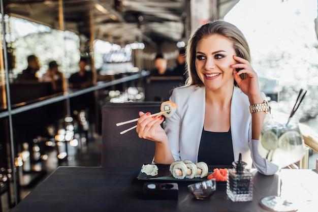 Donna bionda che mangia sushi usando le bacchette espressione di paura, spaventata in silenzio.