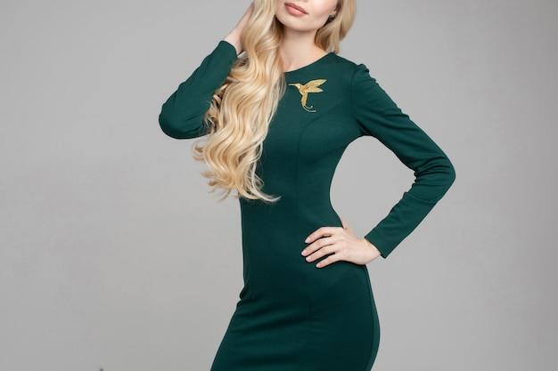 Donna bionda in abito verde smeraldo con spilla colibrì.