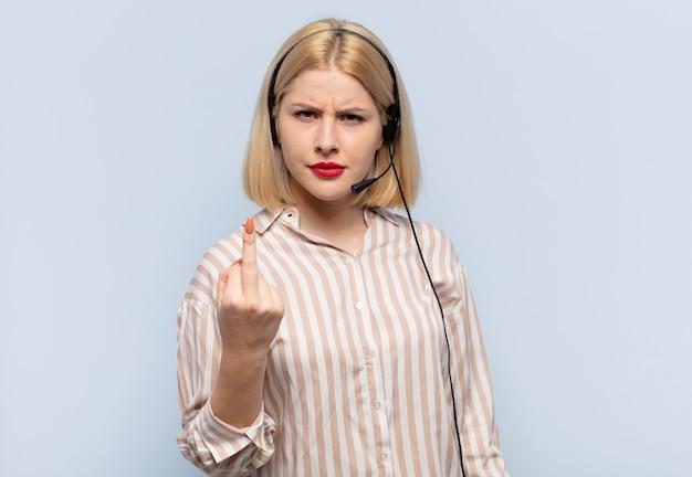 Donna bionda che si sente arrabbiata, infastidita, ribelle e aggressiva, lancia il dito medio, reagisce