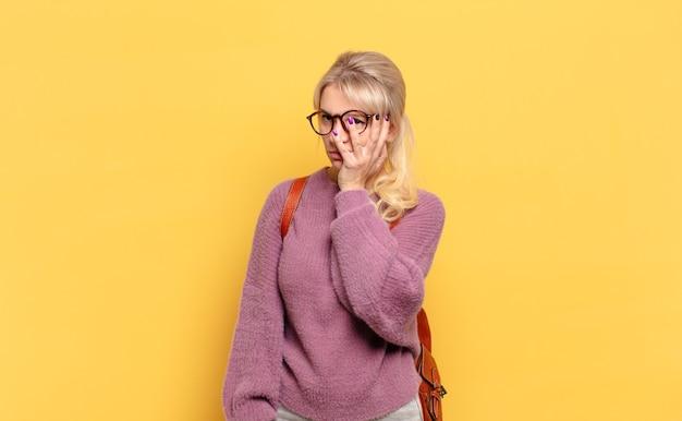 Donna bionda che si sente annoiata, frustrata e assonnata dopo un compito noioso, noioso e noioso, tenendo la faccia con la mano