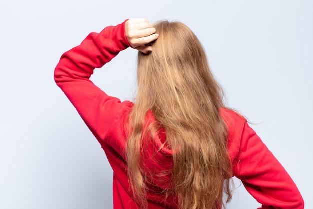 Donna bionda che si sente incapace e confusa, pensando a una soluzione, con una mano sull'anca e l'altra sulla testa, vista posteriore