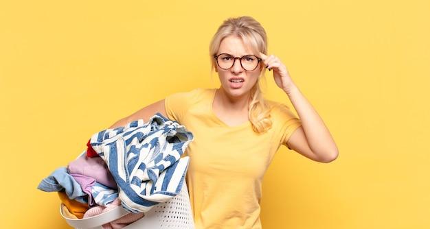 Donna bionda che si sente confusa e perplessa, dimostrando che sei pazzo, pazzo o fuori di testa