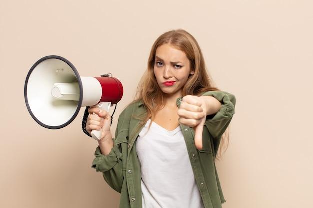 Donna bionda che si sente arrabbiata, arrabbiata, infastidita, delusa o scontenta, mostrando i pollici verso il basso con uno sguardo serio