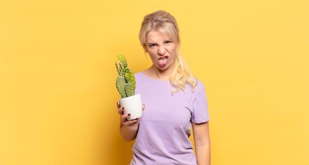 Donna bionda che si sente disgustata e irritata, tira fuori la lingua, tiene in mano una pianta