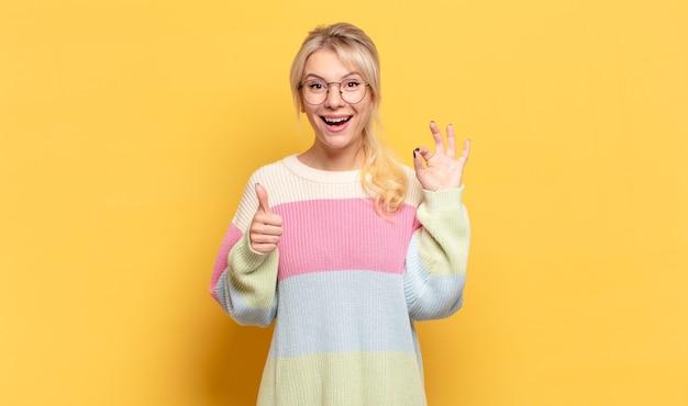 Donna bionda che si sente felice, stupita, soddisfatta e sorpresa, mostrando gesti ok e pollice in alto, sorridendo