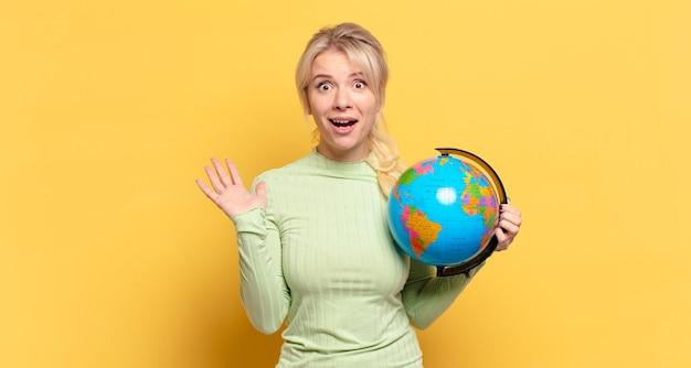 Donna bionda che si sente felice, eccitata, sorpresa o scioccata, sorridente e stupita per qualcosa di incredibile