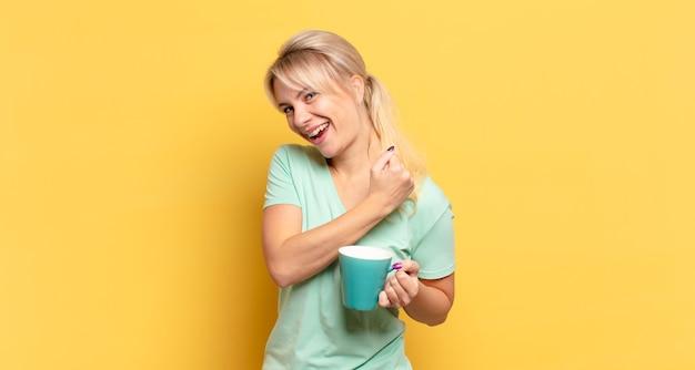 Donna bionda che si sente felice, positiva e di successo, motivata quando affronta una sfida o celebra buoni risultati