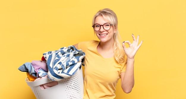 Donna bionda che si sente felice, rilassata e soddisfatta, mostrando approvazione con un gesto ok, sorridendo