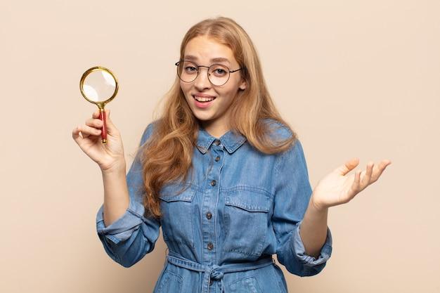 Donna bionda che si sente felice, sorpresa e allegra, sorridente con atteggiamento positivo, realizzando una soluzione o un'idea