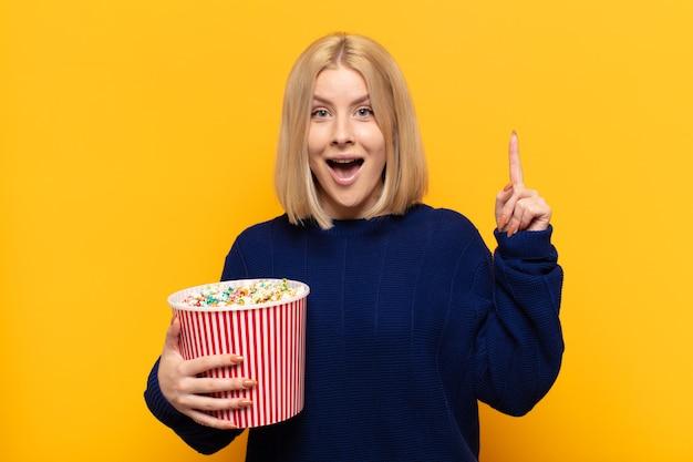 Donna bionda che si sente come un genio felice ed eccitato dopo aver realizzato un'idea, alzando allegramente il dito, eureka!