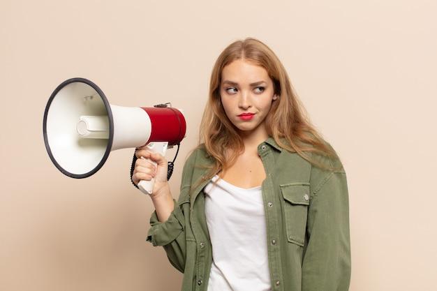 Donna bionda che si sente triste, arrabbiata o arrabbiata e guarda di lato con un atteggiamento negativo, aggrottando la fronte in disaccordo