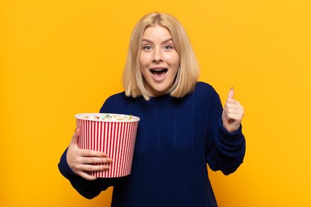 Donna bionda che si sente scioccata, eccitata e felice, ride e celebra il successo, dicendo wow!