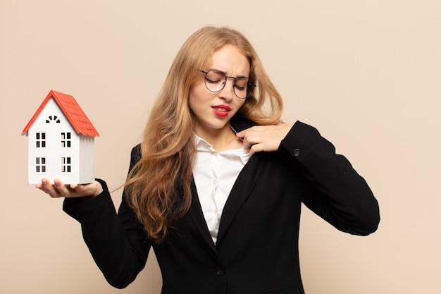 Donna bionda che si sente stressata, ansiosa, stanca e frustrata, tirando il collo della camicia