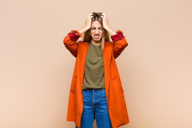 Donna bionda che si sente stressata e frustrata, alza le mani sulla testa, si sente stanca, infelice e con emicrania
