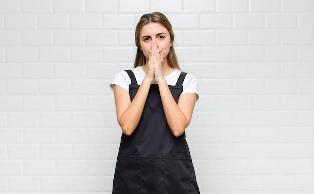 Donna bionda che si sente preoccupata, fiduciosa e religiosa, pregando fedelmente con i palmi premuti, chiedendo perdono