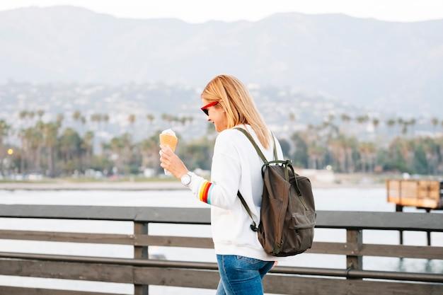 Una donna bionda con gli occhiali gode del gelato al tramonto su un molo della california con le palme sotto i raggi del sole