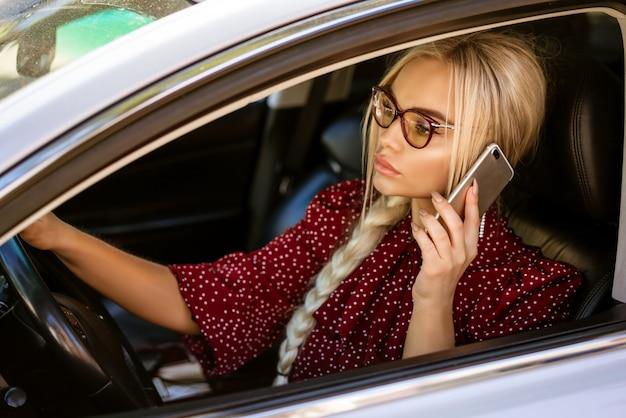 Una donna bionda con gli occhiali e una camicetta rossa si siede al volante e risolve questioni di lavoro utilizzando il telefono.