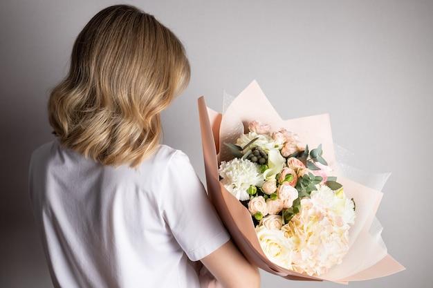 Donna bionda azienda bouquet di fiori contro il muro grigio