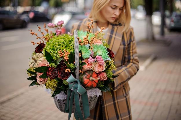 Donna bionda che tiene un cestino di vimini adorabile dei fiori contro la città