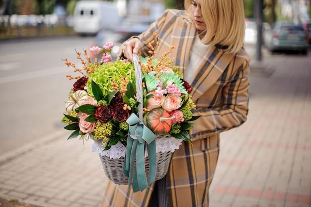 Donna bionda che tiene un cestino di vimini dei fiori di autunno contro la città