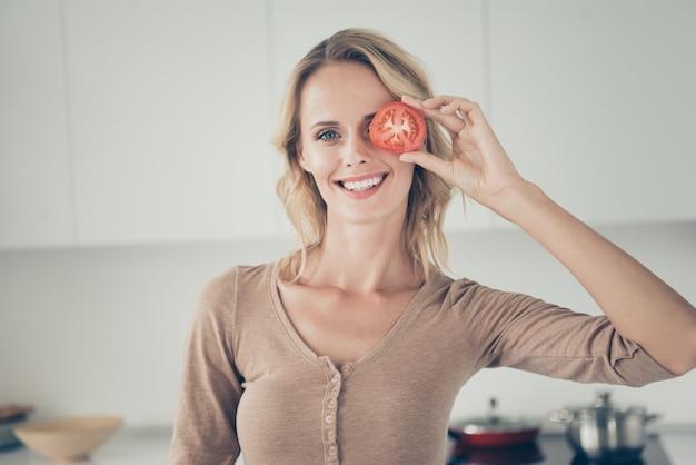Donna bionda a casa in cucina con le verdure