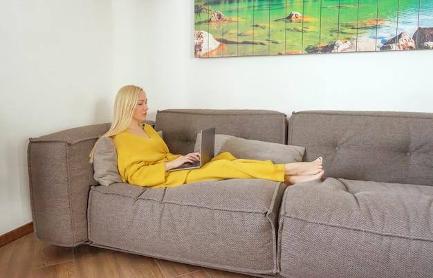 Una donna bionda sta tenendo il laptop e sta lavorando a casa. colori alla moda. colori dell'anno 2021