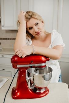 Donna bionda è in posa appoggiato su un mixer stand rosso durante frustate ingredienti in cucina