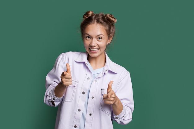 La donna bionda sta sorridendo e indicando la macchina fotografica che indossa vestiti di jeans su una parete verde dello studio