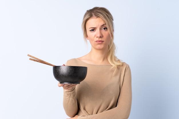 Donna bionda sopra il blu isolato con espressione triste mentre si tiene una ciotola di spaghetti con le bacchette