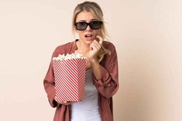 Donna bionda sopra la parete isolata con gli occhiali 3d e che tiene un grande secchio di popcorn
