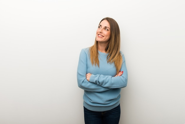 Donna bionda su fondo bianco isolato che osserva mentre sorridendo