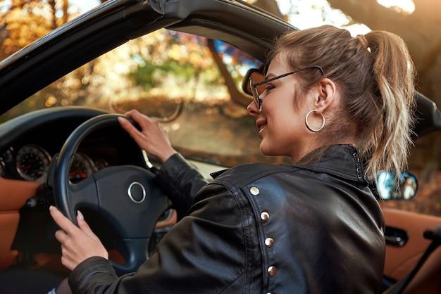 Donna bionda in giacca di pelle in cabriolet che indossa occhiali da sole vista posteriore