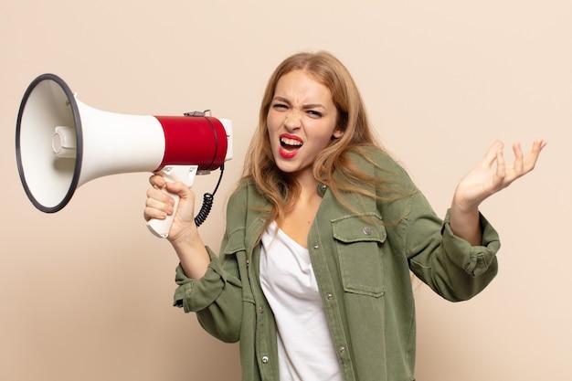 Donna bionda che sembra arrabbiata, infastidita e frustrata che grida wtf