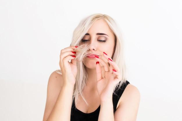 Donna bionda che esamina le punte dei capelli