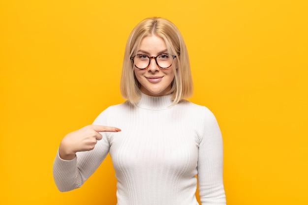 Donna bionda che sembra orgogliosa, sicura e felice, sorridente e indicando se stessa o facendo il segno numero uno