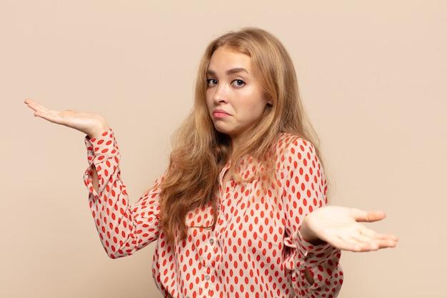 Donna bionda che sembra perplessa, confusa e stressata, chiedendosi tra diverse opzioni, sentendosi incerta