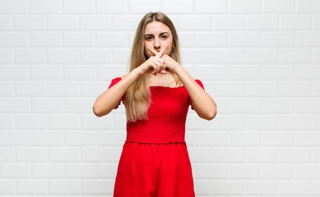 Donna bionda che sembra seria e scontenta con entrambe le dita incrociate davanti in segno di rifiuto, chiedendo silenzio