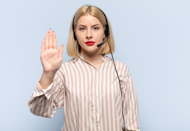 Donna bionda che sembra serio, severo, dispiaciuto e arrabbiato che mostra il palmo aperto che fa il gesto di arresto