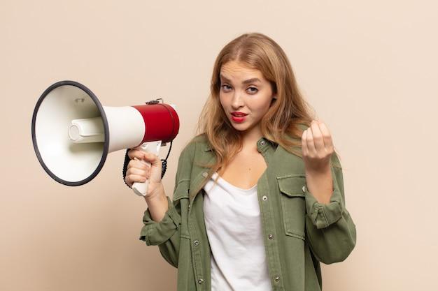 Donna bionda che fa capice o gesto di denaro, dicendoti di pagare i tuoi debiti!
