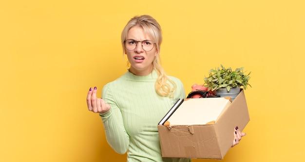 Donna bionda che fa gesto di capice o denaro, dicendoti di pagare i tuoi debiti!
